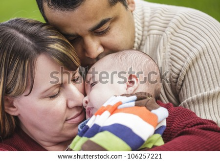 Happy Mixed Race Parents Hugging Their Son in the Park.
