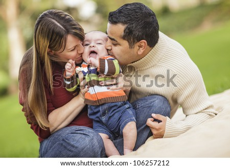 Happy Mixed Race Parents Playing with Their Giggling Son.