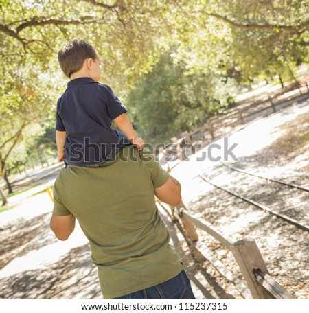 Happy Mixed Race Son Enjoys a Piggy Back Ride in the Park with Dad.