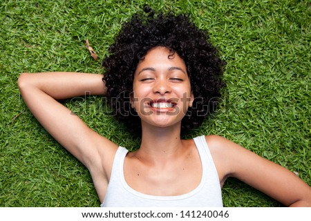 Happy mixed race woman lying down on green grass with hands behind her head.