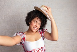 Happy mixed race woman with curly hair in typical plaid dress and straw hat. Taking a photograph, selfie. Festa Junina in Brazil, known as brazilian June Party