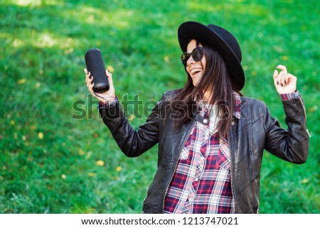 Happy mixed race young woman listening to music with wireless portable speaker. Hispanic hipster girl dancing to rhythm and singing along melody in the park
