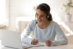 Happy mixed race young woman wearing headset, looking at laptop screen, watching educational lecture, enjoying interesting webinar, writing notes. Smiling employee holding video call with clients.