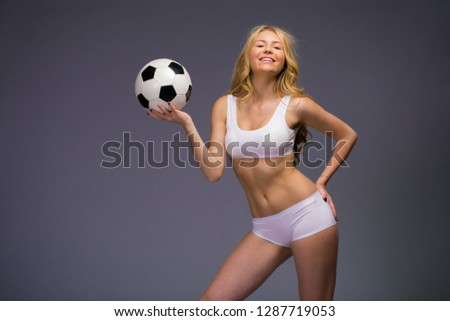 139786ef0 Happy model holding a soccer ball. Young beautiful blonde woman in white  fitness clothing