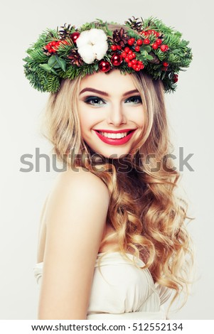 Happy Model Woman with Christmas Wreath. Beautiful Woman with Blonde Hairstyle and Makeup