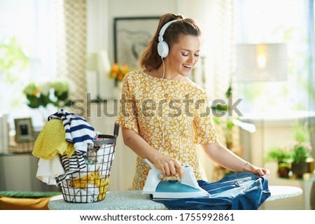 Photo of  happy modern middle age woman in yellow dress with washed clothes basket ironing on ironing board while listening to the music with headphones in the modern house in sunny day.