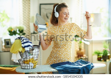 happy modern middle age woman in yellow dress with washed clothes basket ironing on ironing board while listening to the music with headphones at modern home in sunny day.