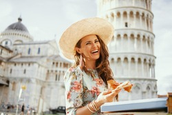 happy modern middle aged traveller woman in floral dress with pizza and hat near Leaning Tower in Pisa, Italy.