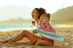 happy modern mother and child in swimwear on the seashore in the evening having fun time wrapped in watermelon towel. minimal to no crowd peace. Fun beach-friendly activities for the whole family.