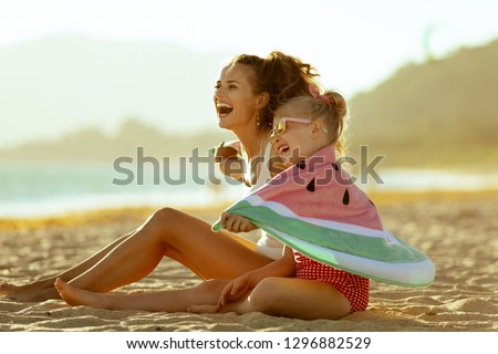 happy modern mother and child in swimwear on the seashore in the evening having fun time wrapped in watermelon towel. minimal to no crowd peace. Fun beach-friendly activities for the whole family. #1296882529