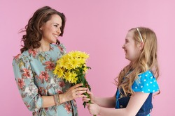 happy modern mother and daughter with long wavy hair presenting yellow chrysanthemums flowers isolated on pink.