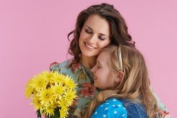 happy modern mother and daughter with long wavy hair with yellow chrysanthemums flowers embracing isolated on pink.