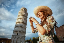 happy modern solo tourist woman in floral dress with film camera and hat near Leaning Tower in Pisa, Italy.