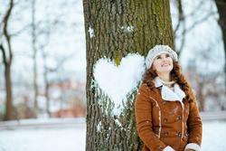 happy modern 40 years old woman in a knitted hat and sheepskin coat near tree with snowy heart outdoors in the city park in winter.