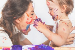 Happy mom and baby playing with painted face by paint. Mother day. Games with child affect early development. Important to spend enough time with your kids.