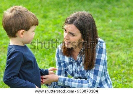Happy mom and son play in the park in spring. Mother Talking to her son in the park