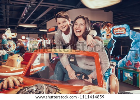 Happy mom and son sitting on toy car. Spending holiday together with family. Entertainment center, mall, amusement park. Family rest, leisure.