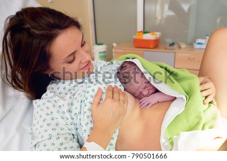 Happy mom, having her baby skin to skin first seconds after birth, happiness family concept