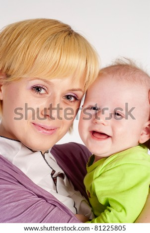 happy mom holds her baby on white