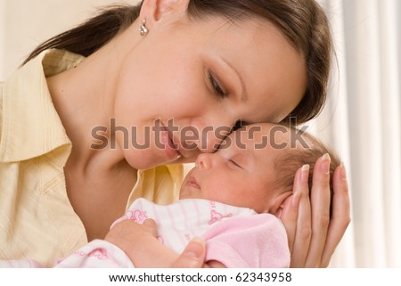 happy mom holds the baby on a white
