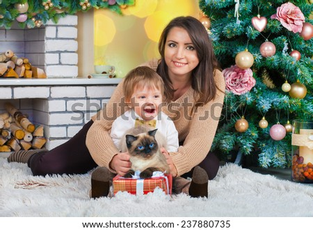 Happy mom, son and cat in the living room near decorated Christmas fir tree and fireplace