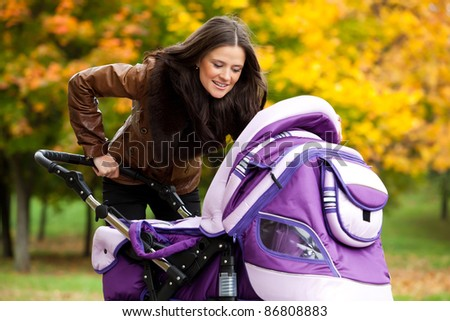 happy mom with stroller walks in park. a bright autumn day.