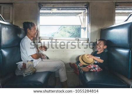Happy moment with big laughing, while travel on ordinary train.  Asian boy explore the new experience with his grand-mother, concept for learning by doing, visual education. #1055284814