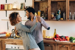 Happy moments. Young african-american couple in love dancing in kitchen, copy space