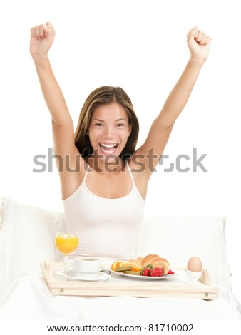 Happy morning breakfast woman smiling eating breakfast in bed stretching looking at camera. Beautiful morning fresh multicultural Asian Caucasian female model isolated on white background.