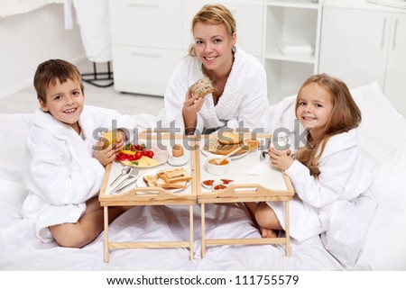 Happy morning - woman and kids having a light breakfast in bed