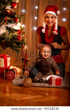 Happy mother and adorable baby in suit of Santa's little helper