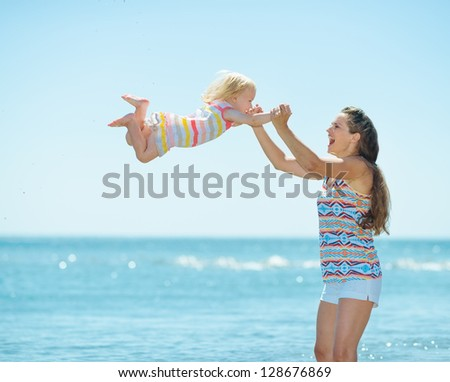 Happy mother and baby girl playing at seaside