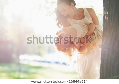 Happy mother and baby having fun near tree