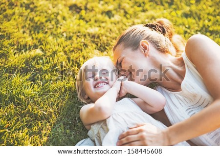Happy mother and baby laying on meadow