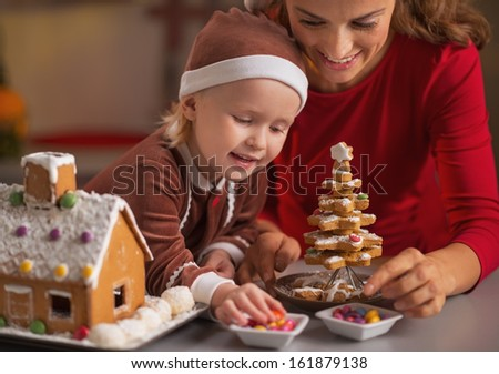 Happy mother and baby making christmas cookie house in kitchen