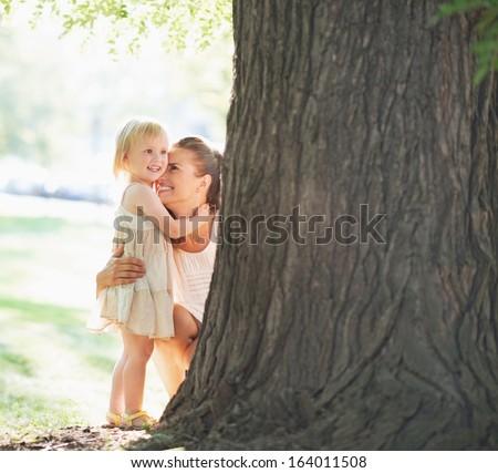 Happy mother and baby near tree - stock photo
