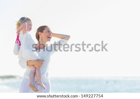 Happy mother and baby on beach looking into distance