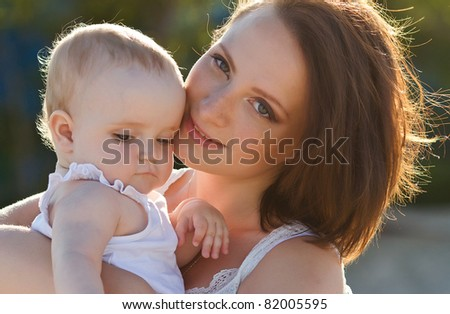 happy mother and baby playing on nature