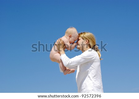 happy mother and baby playing on sky background
