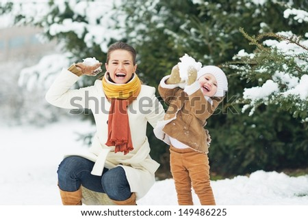 Happy mother and baby throwing snowballs in winter park