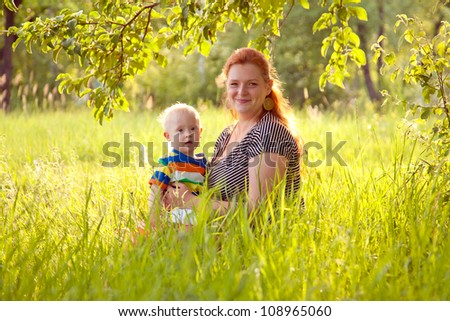 Happy mother and baby with Down syndrome are sitting on the grass in the park.