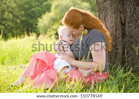 Happy mother and baby with Down syndrome hugging and kissing under the tree on the grass in the park.