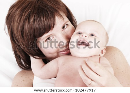Happy mother and child lying into the bed