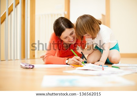 Happy mother and child sketching  on paper at parquet floor
