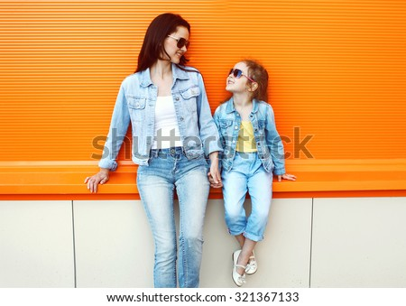 Happy mother and child wearing a jeans clothes in city #321367133