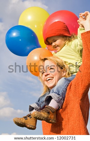 Happy mother and cute child playing with balloons #12002731