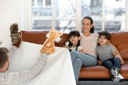 Happy mother and cute little kids watching puppet show at home, young father holding marionette toys showing theater performance for family children having fun in living room enjoy leisure activity