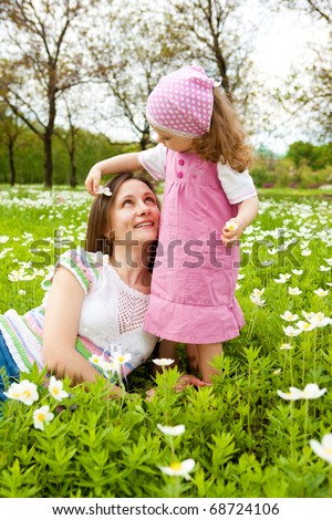 Happy mother and daughter among white flowers