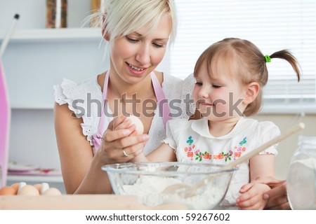 Happy mother and daughter baking together in the kitchen