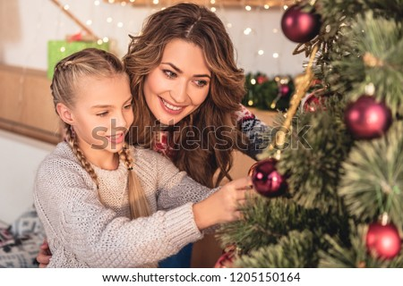 happy mother and daughter decorating christmas tree with baubles at home
